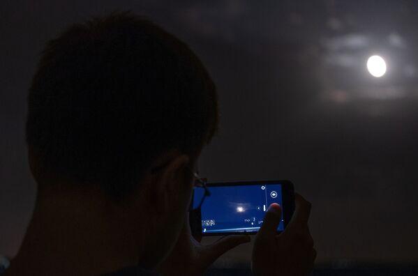 Muž fotografuje měsíc na telefon během úplného zatmění v observatoře Kubanské státní univerzity - Sputnik Česká republika