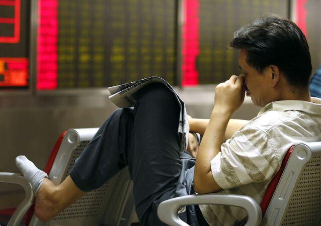 Čínský investor sleduje kurz akcií v Pekingu. Ilustrační foto