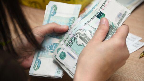 Pracovnice přepočítává peníze. Ilustrační foto - Sputnik Česká republika