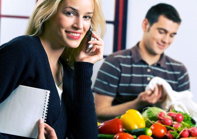 Žena s mobilem a muž s potravinami