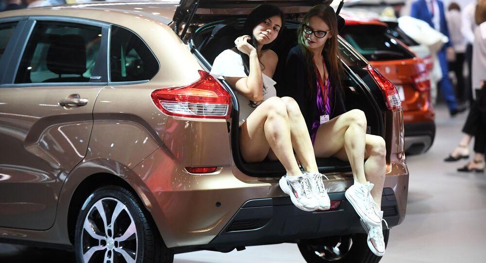 Modelky vedle stánku AvtoVAZu během Moscow International Automobile Salon 2018