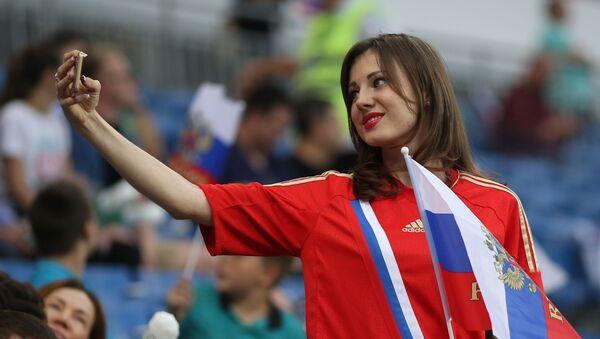 Dívka se fotí na tribunách před zahájením přátelského fotbalového utkání mezi Českem a Ruskem. - Sputnik Česká republika