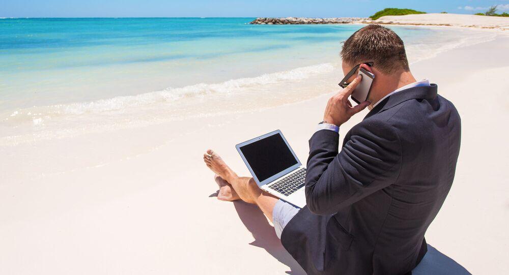 Podnikatel s notebookem na pláži