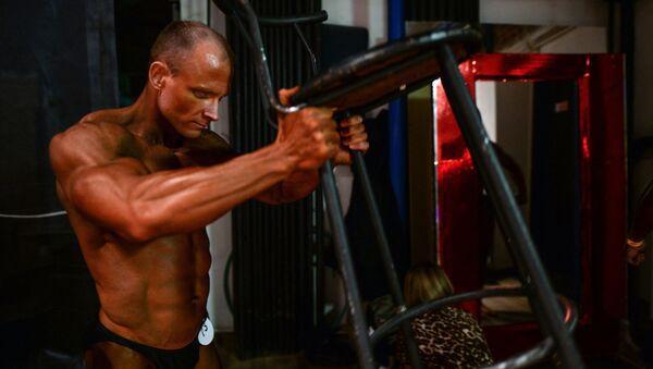Účastník šampionátu Sibiře v bodybuildingu, fitnessu a bodyfitnessu se připravuje na vystoupení - Sputnik Česká republika