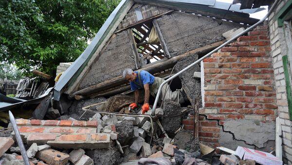 Záchranář se snaží najít ženu pod troskami jejího domu nedaleko Horlivky. Archivní foto - Sputnik Česká republika