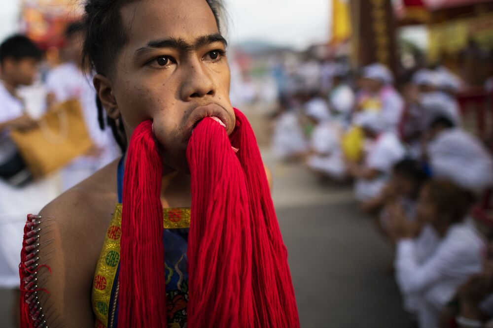 Účastník festivalu, kterému skrz velké díry v tvářích trčí příze.