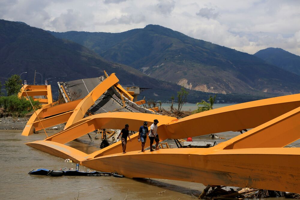 Lidé procházející se po zdevastovaném mostě, který zničilo zemětřesení a tsunami (Sulawesi, Indonésie).