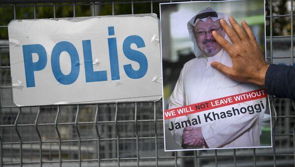Účastník protestní akce s portrétem saúdského novináře Chášakdžího před budovou konzulátu Saúdské Arábie v Istanbulu - Sputnik Česká republika