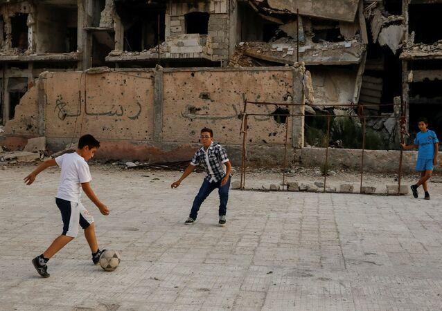 Chlapci hrají fotbal na ulici