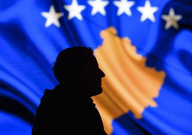 Muž na pozadí vlajky Kosova.