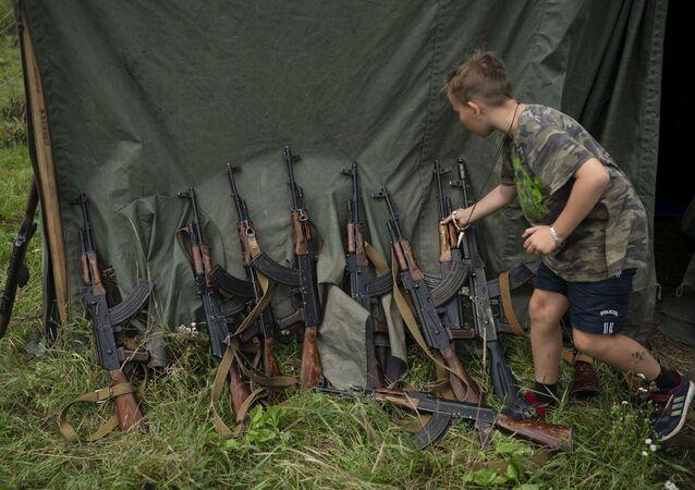 Kluk vedle útočných pušek AK-47 ve vojensky organizovaném kempu u Ternopilu