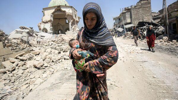 Iráčanka s dítětem naproti zničené mešitě v Mosulu - Sputnik Česká republika