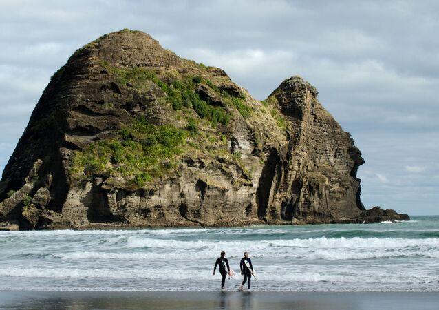 Surfaři na pláži v Novém Zélandu