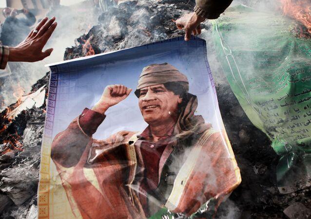 Obyvatelé Benghází podpalují portrét Muammara Kaddáfiho.