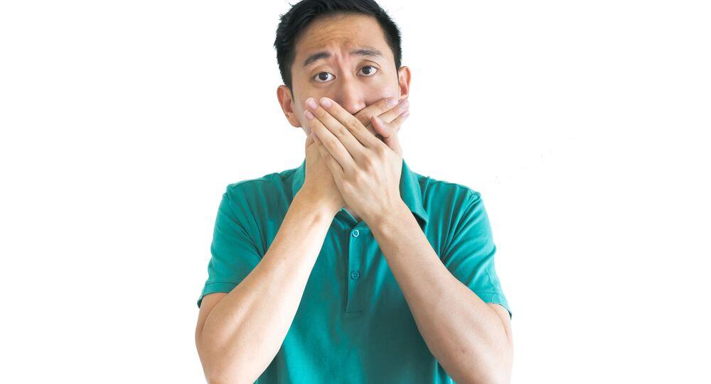 Asijský muž pokrývá ústa
