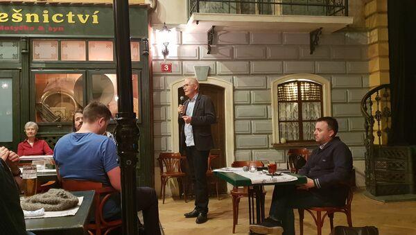 Moderátor představuje novináře Ondřeje Kundru, který sedí u stolu a čeká na slovo - Sputnik Česká republika