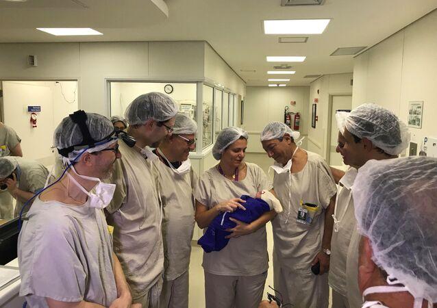Lékaři s dídětem, které porodila žena po transplantaci dělohy od mrtvého dárce