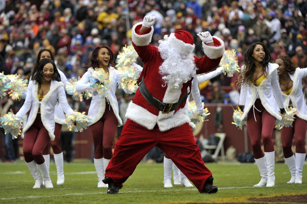 Roztleskávačky fotbalového týmu Washington Redskins vystupují se Santa Klausem během fotbalového zápasu NFL mezi New York Giants a Washington Redskins, USA