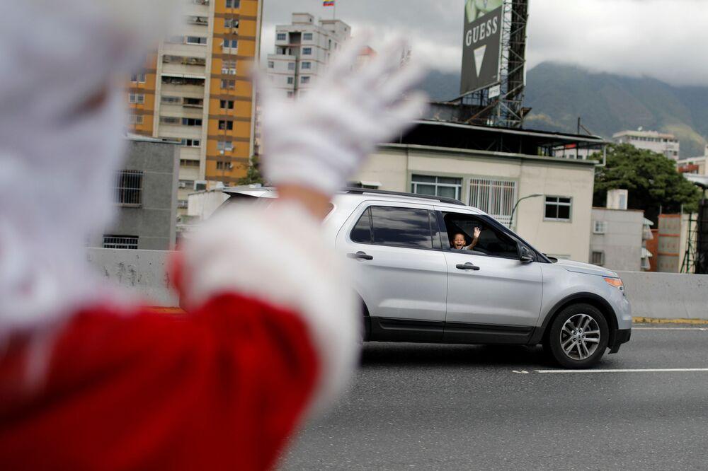 Účastník události Santa en las calles mává dítěti v Caracasu, Venezuela