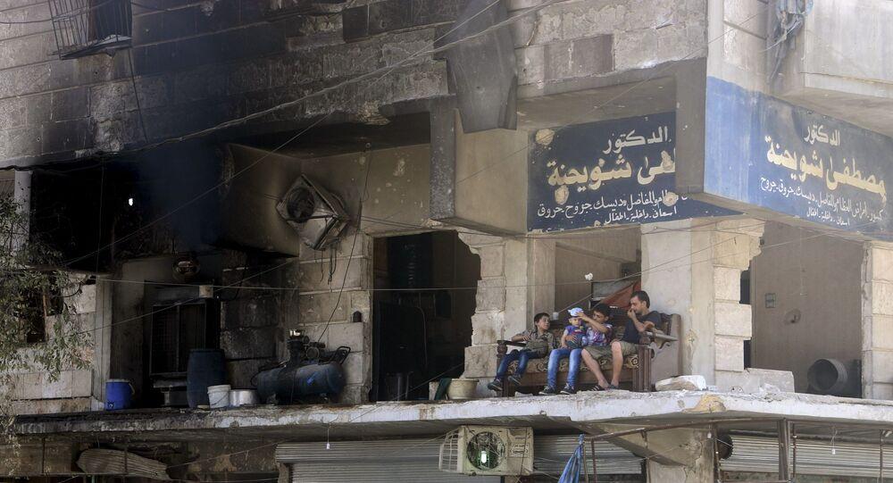 Místní obyvatelé sedí na balkonu zničeného domu v Aleppu