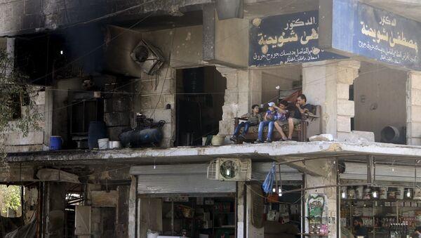 Místní obyvatelé sedí na balkonu zničeného domu v Aleppu - Sputnik Česká republika