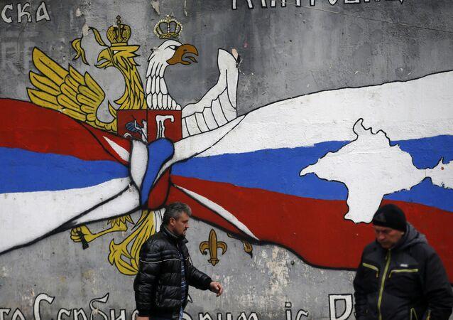 Graffiti v Mitrovici s vlajkami Ruska a Kosova a mapami Krymu a Kosova