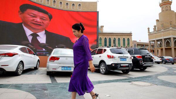 Ujgurka prochází kolem velké obrazovky s čínským prezidentem Si Ťin-pchingem na náměstí v Kašgar v Ujgurské autonomní oblasti Sin-ťiang. - Sputnik Česká republika