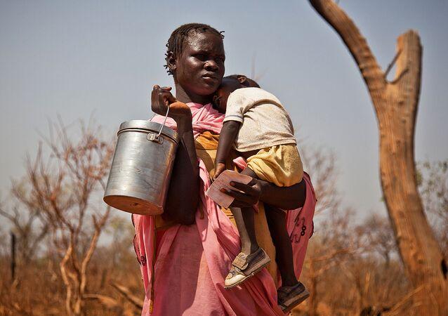 Jihosúdánská žena s dítětem a plechovkou v ruce