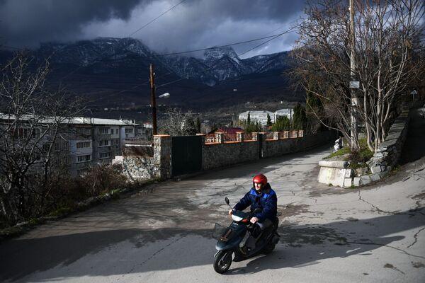Muž jede na mopedu v Gurzufu na Krymu - Sputnik Česká republika