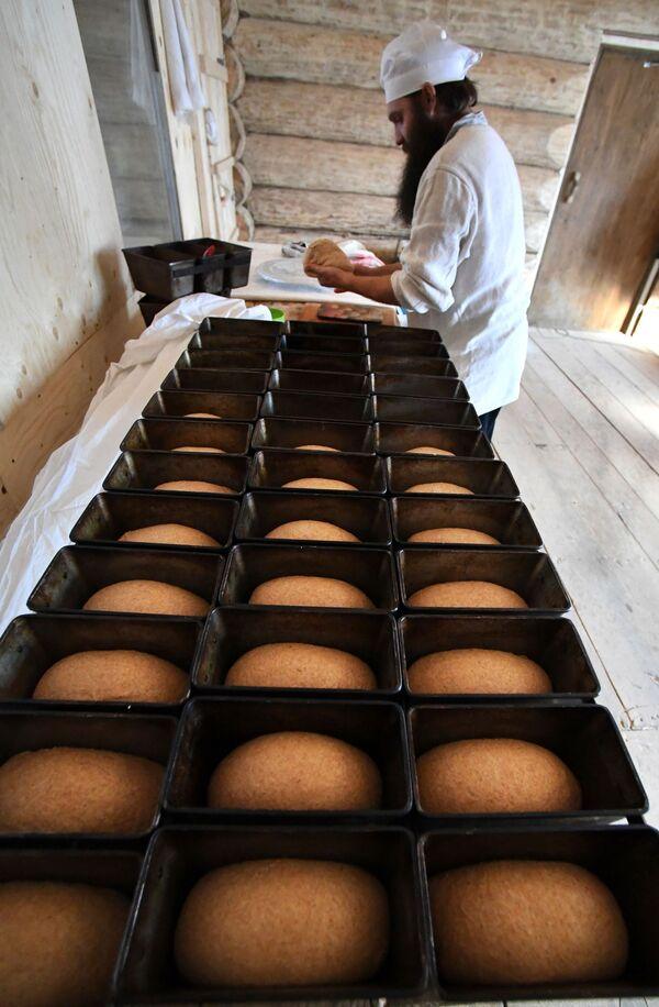 Пекарь Павел Русов раскладывает тесто по формам в пекарне Хлеб-отец - Sputnik Česká republika