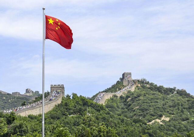 Čínská vlajka na pozadí Velké čínské zdi