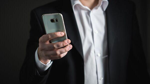 Мужчина держит мобильный телефон - Sputnik Česká republika