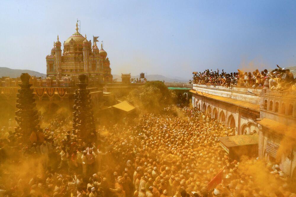 Věřící rozprašují kurkumu jako dar během oslav svátku Somavit Amavasi v Indii.