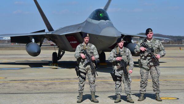 Američtí vojáci na pozadí stíhačky F-22 na vojenské základně v Jižní Koreji - Sputnik Česká republika