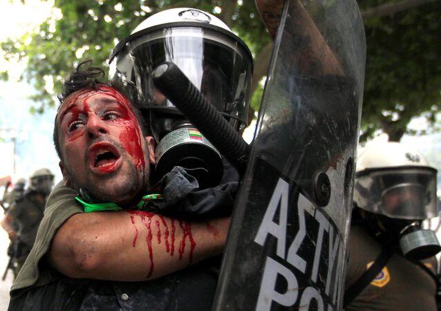 Demonstranta zadržuje policie během protestů proti úsporným opatřením.