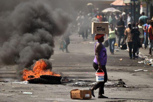 Žena prochází okolo hořící pneumatiky Port-au-Prince, Haiti - Sputnik Česká republika