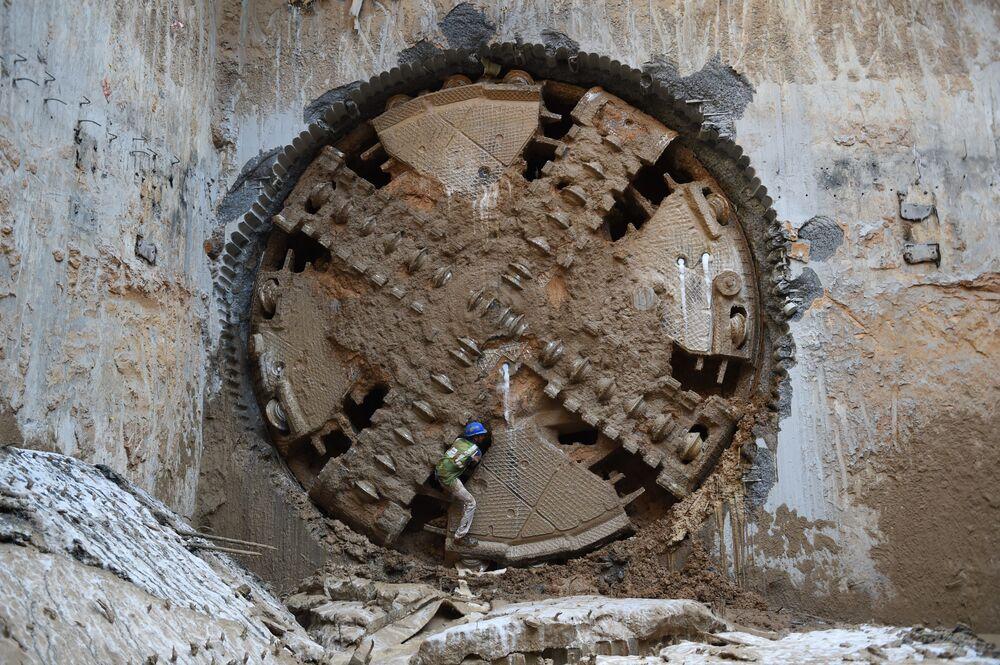 Dělník v blízkosti vrtacího stroje na výstavbě tunelu pro metro v Ahmadábádu, Indie