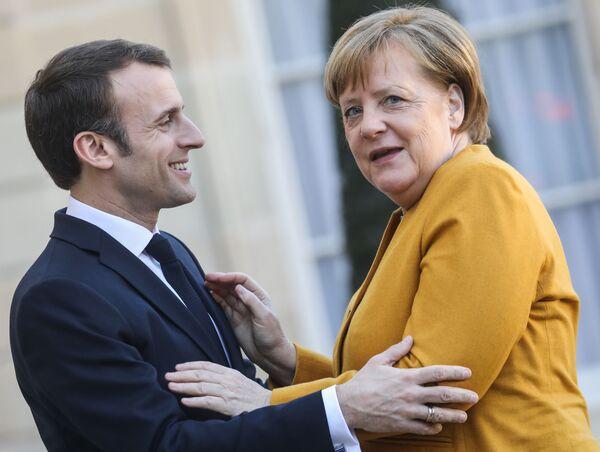 Francouzský prezident Emmanuel Macron a německá kancléřka Angela Merkelová před zahájením pracovního setkání v Paříži - Sputnik Česká republika