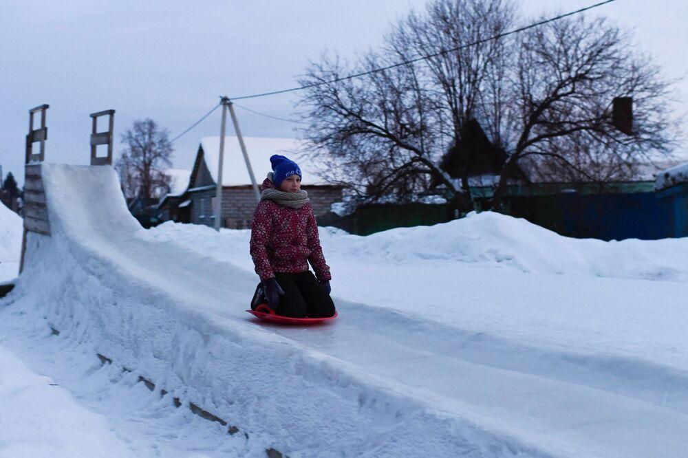 Dívka sjíždí po ledové skluzavce v ruském městě Tara. Omská oblast