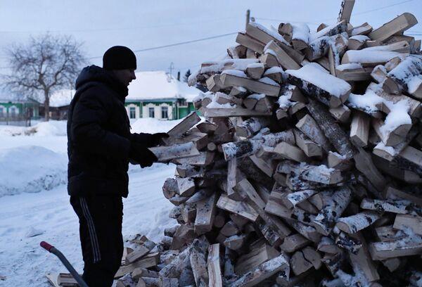 Muž sbírá dříví ve městě Tara - Sputnik Česká republika