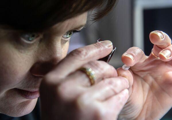 Zaměstnankyně hodnotí diamant v dílně technické kontroly a hodnocení společnosti Brilianty Alrosa s. r. o. v Moskvě - Sputnik Česká republika