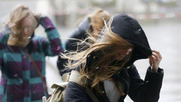 Dívka se snaží schovat před větrem. Ilustrační foto - Sputnik Česká republika