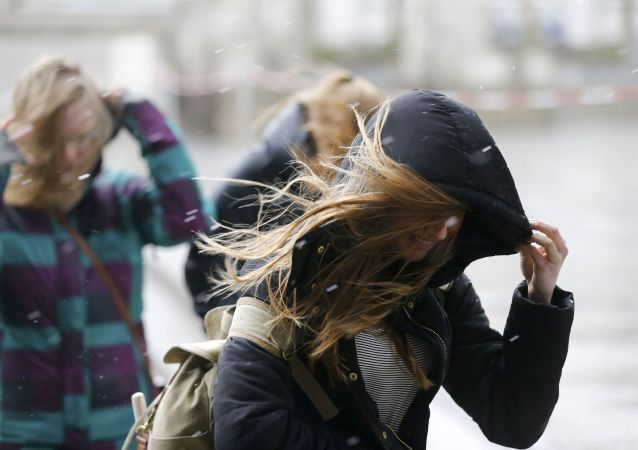 Dívka se snaží schovat před větrem. Ilustrační foto