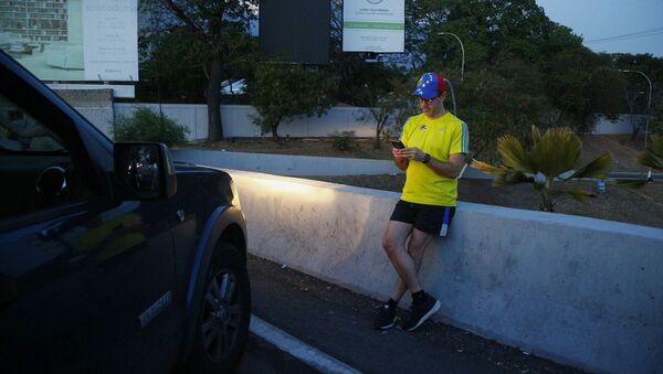 Občan Caracasu se snaží chytit mobilní signál - Sputnik Česká republika
