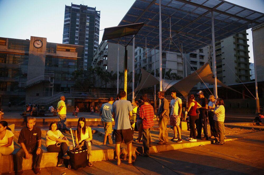 Lidé stojí ve frontě k akumulátoru se solárním panelem na náměstí v Caracasu, aby mohli nabít telefony