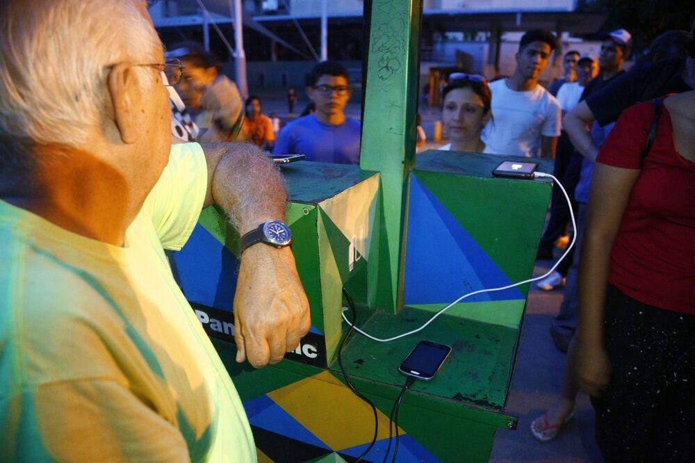 Nabíjení telefonů akumulátorem se solárním panelem na náměstí v Caracasu