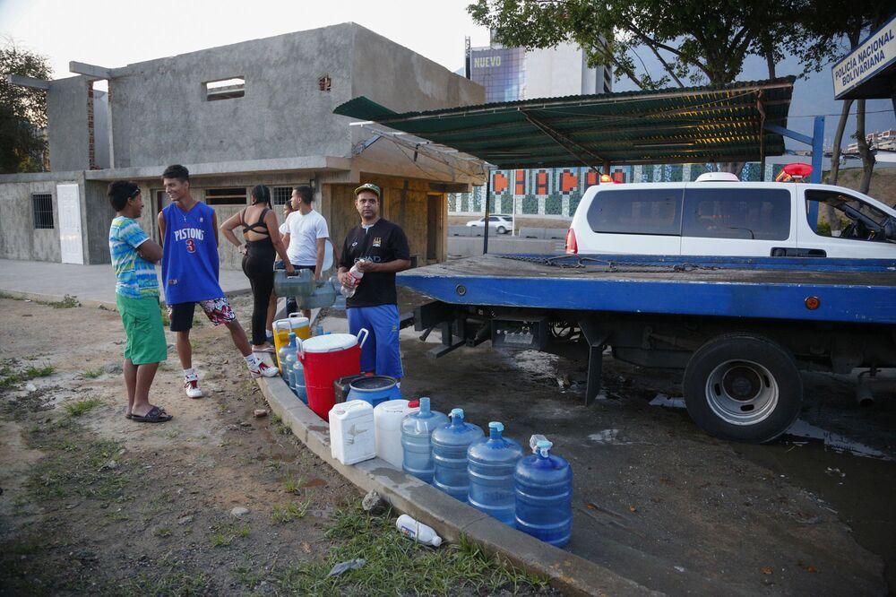 Obyvatelé Caracasu stojí ve frontě, aby dostali vodu do lahví a kanystrů