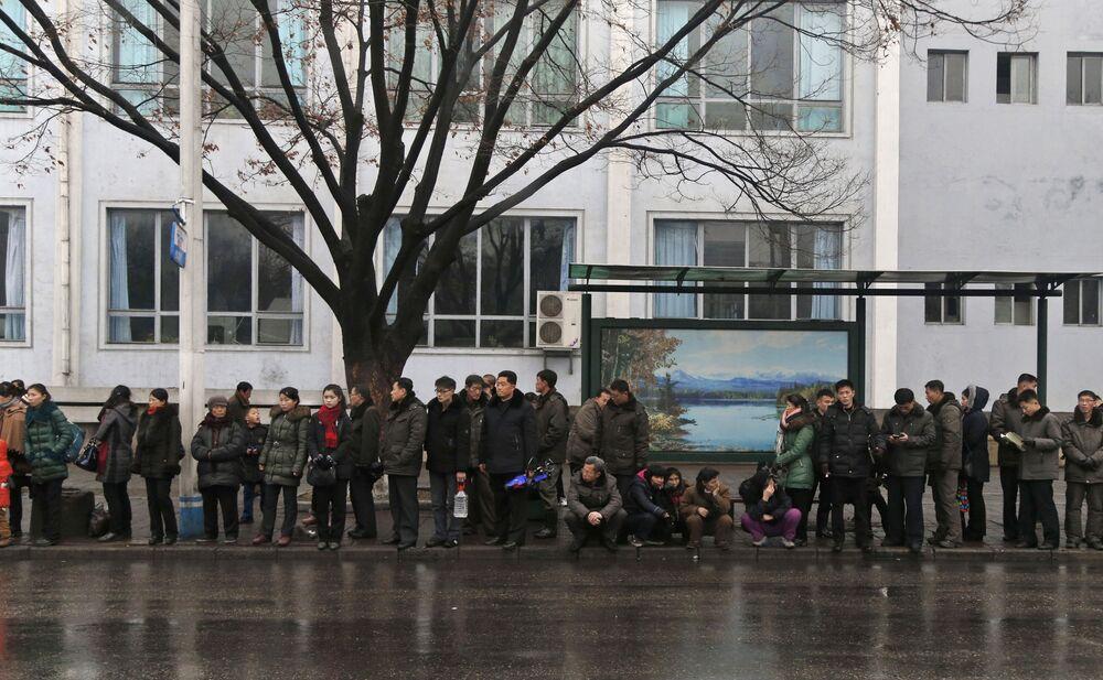 Lidé čekající na trolejbus na jedné ze zastávek v Pchjongjangu, KLDR.