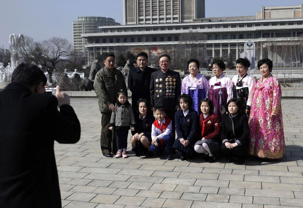 Různé generace jedné rodiny se fotografují v centru Pchjongjangu u příležitosti Mezinárodního dne žen.