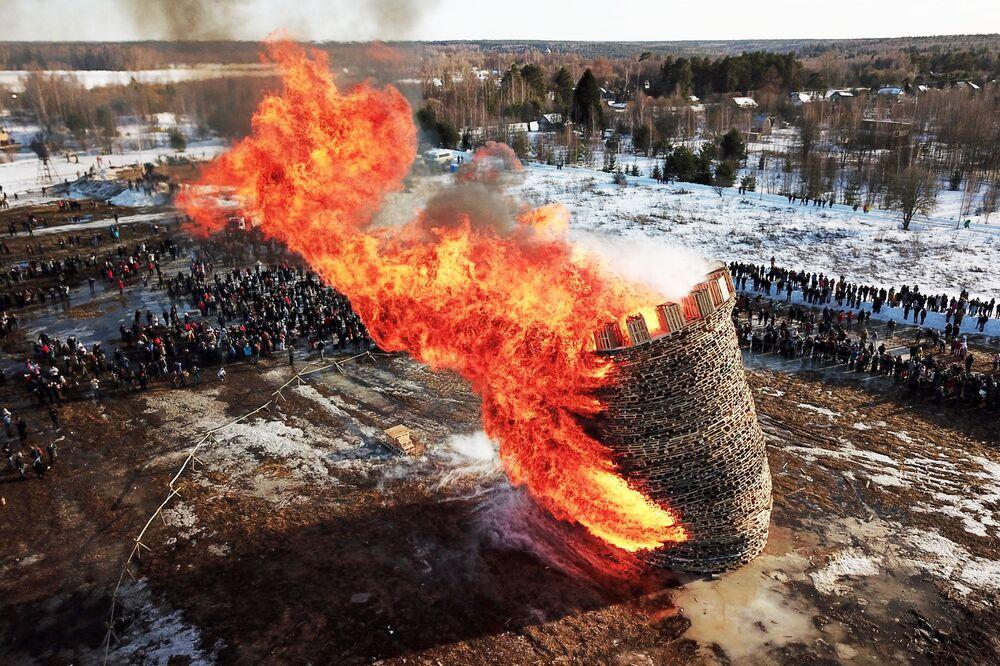Účastníci oslavy Široké Maslenicy při spalování Bastily na území vesnice Nikola-Lenivec.